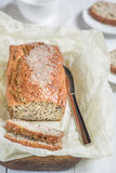 Frisch gebackenes Brot mit Samen des indischen Sesams auf einem hölzernen Brett auf einem lig Lizenzfreie Stockfotos