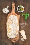 Frisch gebackenes ciabatta Brot mit Knoblauch, Mittelmeeroliven, Basilikum und Parmesankäseparmesankäse auf Umhüllung verschalen  Lizenzfreie Stockbilder
