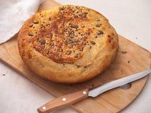 Frisch gebackenes rund-förmiges selbst gemachtes Brot mit Samen und indischem Sesam auf einem hölzernen Brett der Küche lizenzfreie stockbilder