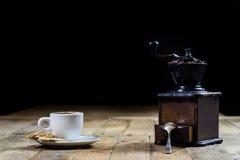 Frisch gebrauter Kaffee in den Schalen auf einem Holztisch mit einem Mahlen Stockbilder