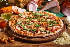 Frisch gekochte Pizza auf dem Holztisch Stockbilder