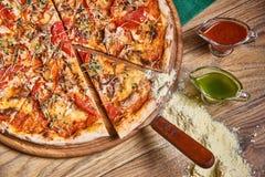 Frisch gekochte Pizza auf dem Holztisch Stockbild
