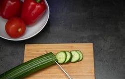 Frisch geschnittene Gurken mit Messer auf hölzernem Schneidebrett mit einer Platte des Paprikas und der Tomate stockfoto