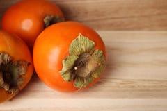Frisch trägt Persimonen in der Holzkiste über hölzernem Hintergrund Früchte mit einem Platz für eine Aufschrift Gesunde Frucht Lizenzfreie Stockbilder