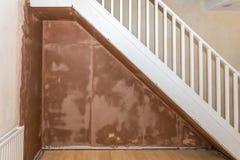 Frisch vergipste Wand unter Treppenhaus in einem inländischen Raum Stockfoto