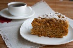 Frisch verzierter organischer Karottenkuchen Nahaufnahme einer Kuchenstruktur Ein Stück des Kuchens mit einem Tasse Kaffee Stockfotos