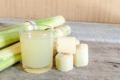 Frisch zusammengedrückter Zuckerzuckerrohrsaft im Glas mit geschnittenem Stückstock Lizenzfreies Stockfoto