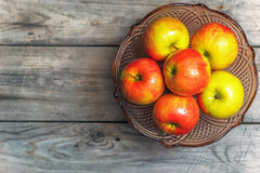 Frische Äpfel in einem dekorativen Vase für Frucht auf einem Holztisch Lizenzfreies Stockfoto