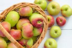 Frische Äpfel ernten in einem Korb auf einem hölzernen Hintergrund Stockfotos