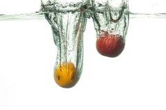 Frische Äpfel und orange Fallen in Wasser Lizenzfreie Stockfotos
