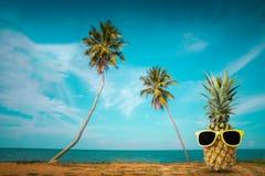 Frische Ananas auf dem Strand, Modehippie-Ananas, helle Sommerfarbe, tropische Frucht mit Sonnenbrille Lizenzfreies Stockbild
