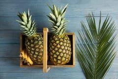 Frische Ananas im Kasten auf hölzernem Hintergrund Lizenzfreie Stockfotos