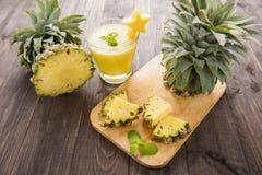 Frische Ananas mit Ananas Smoothie auf Holztisch Lizenzfreies Stockfoto