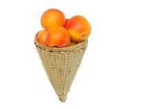 Frische Aprikose gehalten im handwoven konischen Korb Stockfotos