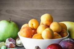 Frische Aprikosen in einem weißen Teller und andere Früchte auf dem Küchentisch Gesunder Lebensstil Stockfoto
