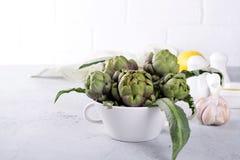 Frische Artischocke, die für das Kochen mit Knoblauch, Zitrone und Olivenöl sich vorbereitet, Lizenzfreie Stockfotografie