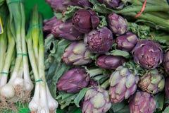 Frische Artischocken und Zwiebeln am Markt Lizenzfreies Stockfoto
