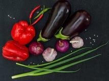 Frische Auberginen, Pfeffer, Knoblauch, Zwiebel auf schwarzem Hintergrund stockfoto