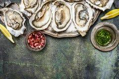 Frische Austern mit Zitrone und verschiedenen Soßen auf rustikalem Hintergrund, Draufsicht, Platz für Text Stockbild