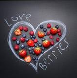 Frische Beeren, Blaubeeren, Erdbeeren und Himbeeren, werden im gezogenen Herzen die Draufsicht der Tafel ausgebreitet Lizenzfreie Stockfotos