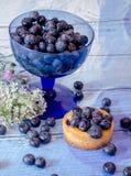 Frische Beeren und Kuchen mit Wildflowers Stockfotos