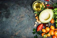 Frische Bestandteile für die Salat- oder Badherstellung: Avocado, Tomaten, Nüsse, Öl auf rustikalem Hintergrund, Draufsicht, Plat Lizenzfreie Stockbilder