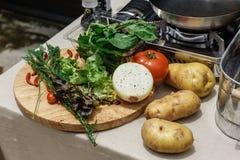 Frische Bestandteile schließen Rosemary, Zwiebel, Tomate, Kartoffel und Gemüse auf hölzernem Block mit ein Stockfoto