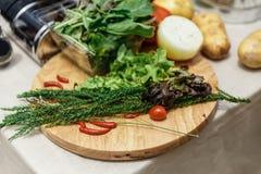 Frische Bestandteile schließen Rosemary, Zwiebel, Tomate, Kartoffel und Gemüse auf hölzernem Block mit ein Stockfotografie