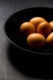 Frische Bio-Eier in der Schüssel auf schwarzem Hintergrund Stockfotos