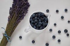 Frische Blaubeeren und trockener Lavendel auf Weiß stockfoto