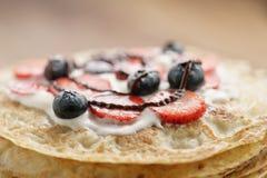 Frische Blinis oder Krepps mit frischen Beeren und der Creme verziert mit Schokoladensoße Lizenzfreies Stockfoto