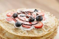 Frische Blinis oder Krepps mit frischen Beeren und der Creme verziert mit Schokoladensoße Stockbilder