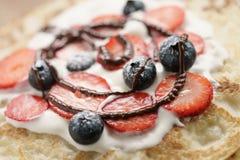 Frische Blinis oder Krepps mit frischen Beeren und der Creme verziert mit Schokoladensoße Stockfoto