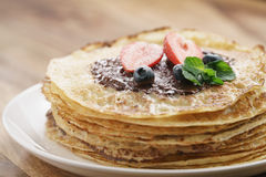 Frische Blinis oder Krepps mit geschmolzener dunkler Schokolade, Beeren und Zuckerpulver Lizenzfreie Stockbilder