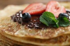 Frische Blinis oder Krepps mit geschmolzener dunkler Schokolade und Beeren Lizenzfreie Stockfotos