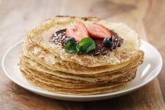 Frische Blinis oder Krepps mit geschmolzener dunkler Schokolade und Beeren Stockfoto