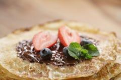 Frische Blinis oder Krepps mit geschmolzener dunkler Schokolade und Beeren Stockbild