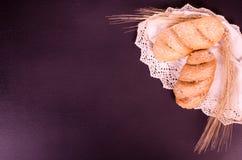 Frische Brötchen, Spitzee und Weizenähren in einem schwarzen Hintergrund Stockfoto