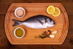 Frische Brachsenfische auf Schneidebrett mit Bestandteilen Lizenzfreies Stockfoto