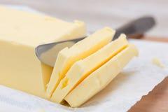 Frische Butter in der Stangenform und in einem Messer Stockfotografie