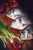 Frische Dorado-Fische auf einem hölzernen Brett mit Gemüse in einem dunklen Schlüssel Stockfoto