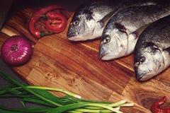 Frische Dorado-Fische auf einem hölzernen Brett mit Gemüse in einem dunklen Schlüssel Lizenzfreies Stockbild