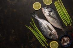 Frische dorado Fische mit Spargel und Gewürzen, Bestandteile für das Kochen auf einem dunklen Hintergrund Draufsicht, Platz für T stockbilder