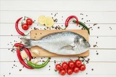 Frische dorado Fische mit Zitrone auf hölzernem Schneidebrett Stockfotos