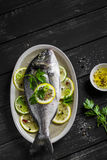 Frische Dorado-Fische mit Zitrone, Kalk und Petersilie auf einem ovalen Teller lizenzfreie stockbilder