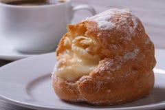 Frische Eclairs mit Vanillepudding auf einer Platte und einem coffee? stockfotografie