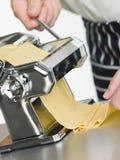 Frische Ei-Teigwaren, die in einer Teigwaren-Maschine gerollt werden stockbild