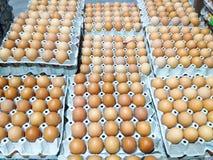 Frische Eier in den braunen Kästen vereinbarten in Staplungsreihen für Verkauf in m Stockfotos