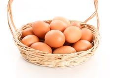 Frische Eier in einem hölzernen Korb auf weißem Hintergrund Stockfotografie