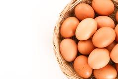 Frische Eier in einem hölzernen Korb auf weißem Hintergrundabschluß oben Stockbild